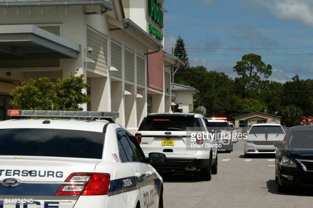 A line of police patrol cars stand by in front of a Publix grocery store location as management closes the store and allows the last shoppers to...