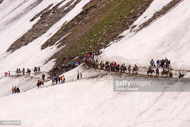 Line of ponies and Hindu pilgrims walking on the Amarnath cave trail, on the snow. Every summer, hundreds of thousands of Hindu devotees do the...