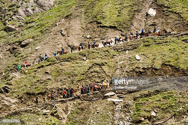 Line of ponies and Hindu pilgrims walking on the steep mountain trail to the Amarnath cave. Every summer, hundreds of thousands of Hindu devotees do...