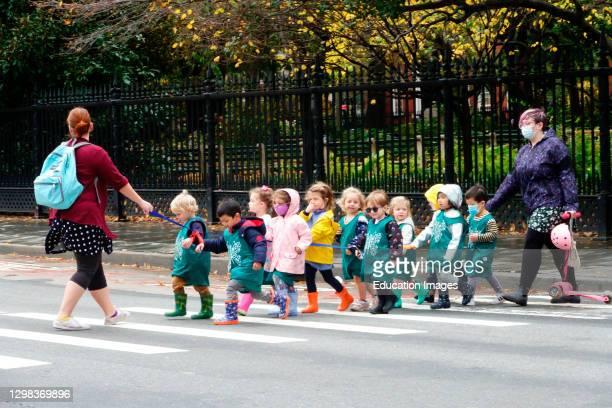 Line of pre-school children crossing street with teacher.