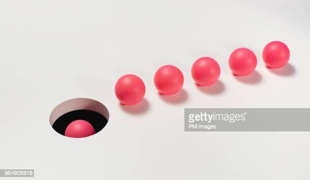 line of red balls heading towards a hole - vaardigheid stockfoto's en -beelden