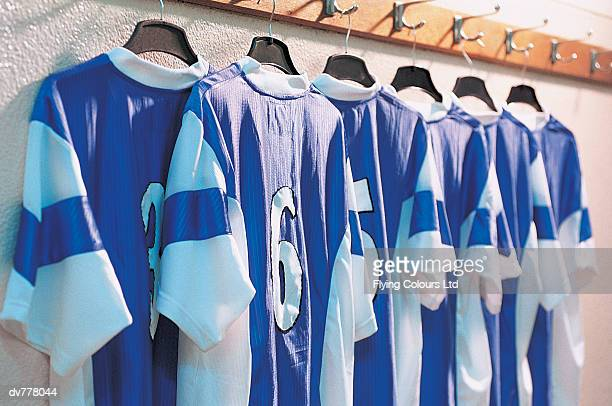 line of rugby shirts hanging from clothes rail - sports jersey stock pictures, royalty-free photos & images