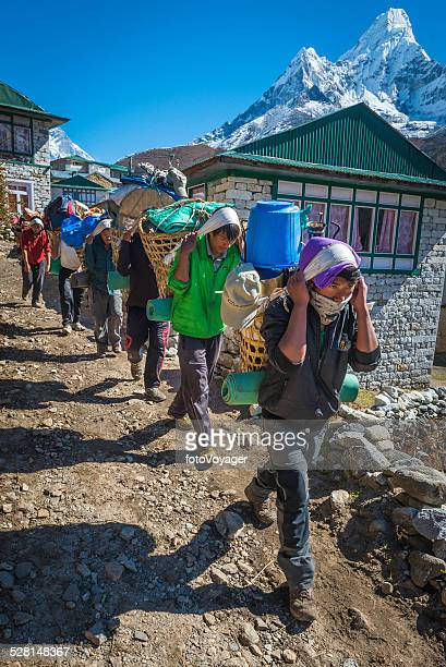 Line of Sherpa porters carrying expedition kit Himalaya mountains Nepal