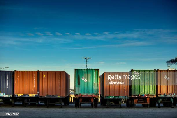 line of shipping containers on trucks - heavy industry stock photos and pictures