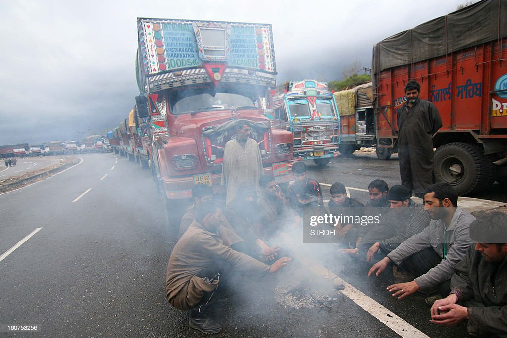 A line of stranded vehicles are pictured as truck drivers warm themselves by a fire while they wait for the reopening of the Jammu-Srinagar national highway in the outskirts of Jammu on February 5, 2013. Kashmir remained cut off from the rest of the country as heavy snowfall in the Pir Panjal mountain range closed the Srinagar-Jammu highway and delayed all scheduled flights to the valley, authorities said. The highway is the only road connection between the landlocked valley and the rest of the country.