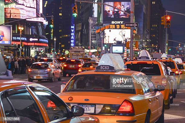 Line of taxis stopped at a red light in Times Square.