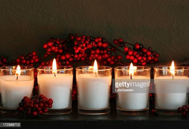 A line of thick candles aflame with dark red berries behind