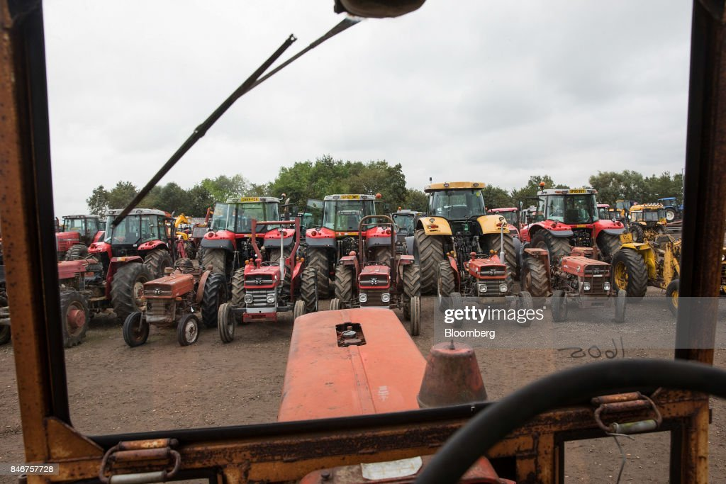 A line of tractors, manufactured by Massey Ferguson Corp., sit parked before they are put up for auction at the Cheffins Cambridge Machinery Sales monthly machinery and plant auction in Sutton, U.K., on Monday, Sept. 4, 2017. The debate over food andfarmingpolicy after Brexit has heated up recently, with Environment Secretary Michael Gove telling BBC Radio 4 that the U.K wouldnt lower its animal welfare or environmental standards to achieve any new trade deals. Photographer: Simon Dawson/Bloomberg via Getty Images