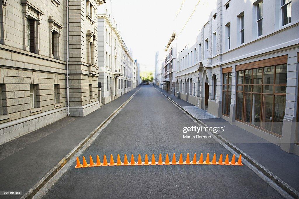 Line of traffic cones in urban roadway : Stock Photo