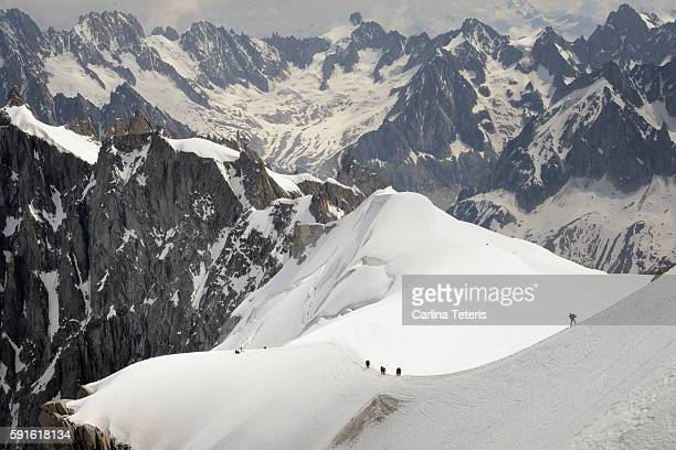 a line of trekkers hiking up a snowy ridge on mont blanc - blanche vallee stock photos and pictures