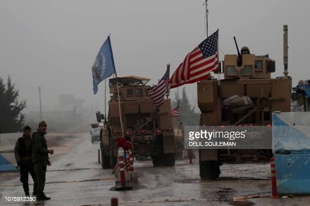 TOPSHOT A line of US military vehicles drive through a checkpoint of the Internal Security Forces in Manbij as they head to their base on the...
