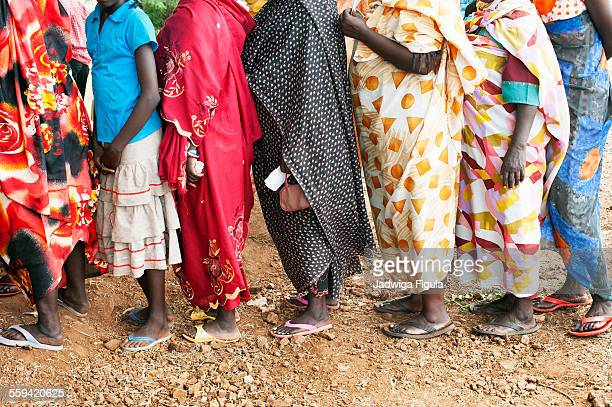 Line of women wearing long and colorful dresses.
