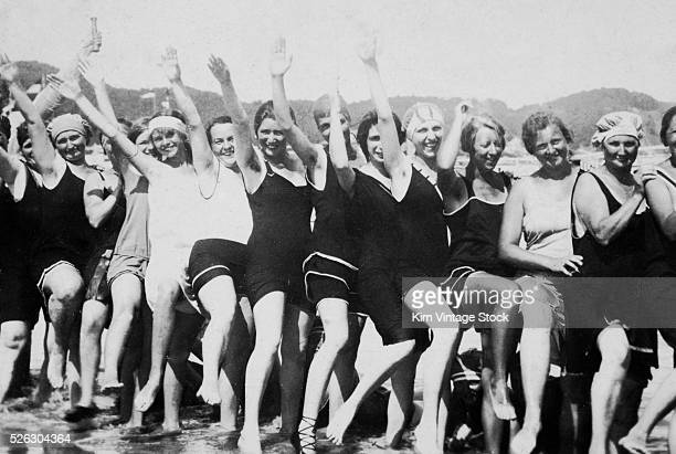 A line of young women show some leg and wave their arms as they party on the beach during the Roaring 20s