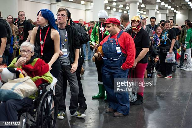 CONTENT] Line or queue for autographs at the New York Comic Con convention including cosplayers costumed as Nintendo's Mario and Marvel's Iron Man...