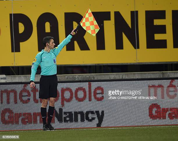 Line referee Gilles Lang gestures during the French L1 football match between Nancy and Angers on December 10 2016 at Marcel Picot stadium in...