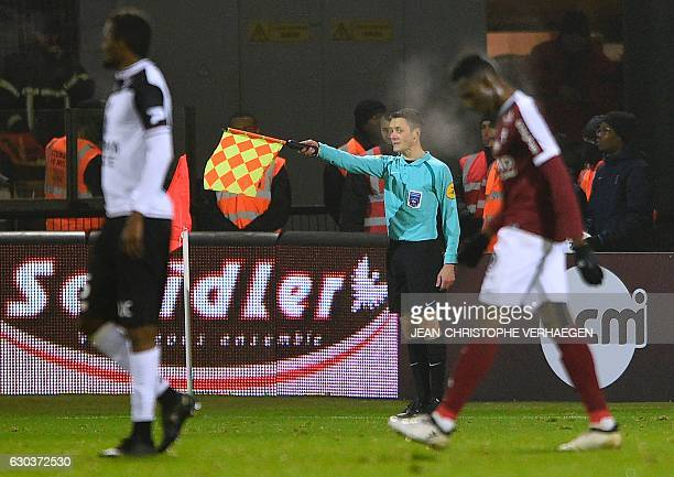 Line referee Gilles Lang gestures during the French L1 football match between Metz and Guingamp on December 21 at the Saint Symphorien stadium in...