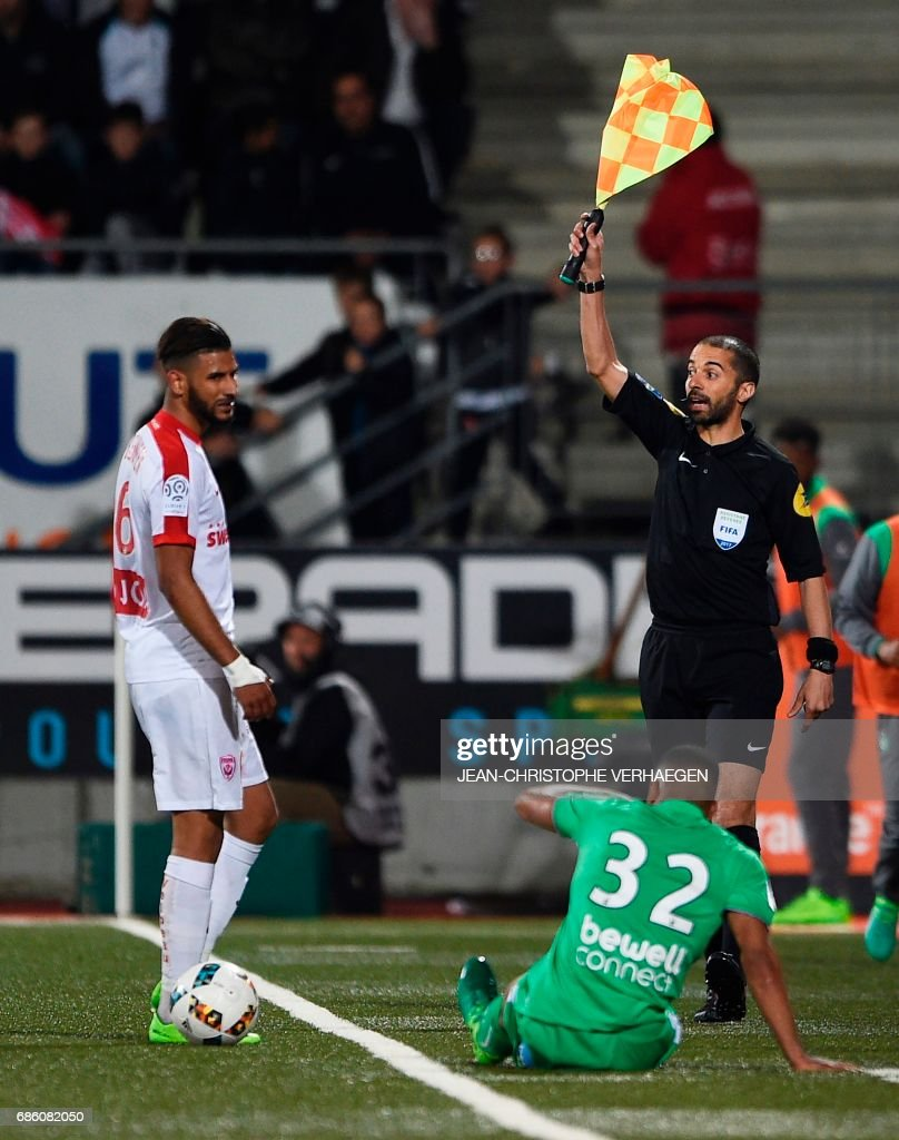 Line referee Hicham Zakrani (R) waves a flag gestures during the French L1 football match between Nancy (ASNL) and Saint-Etienne (ASSE) on May 20, 2017 at Marcel Picot stadium in Tomblaine, eastern France. /