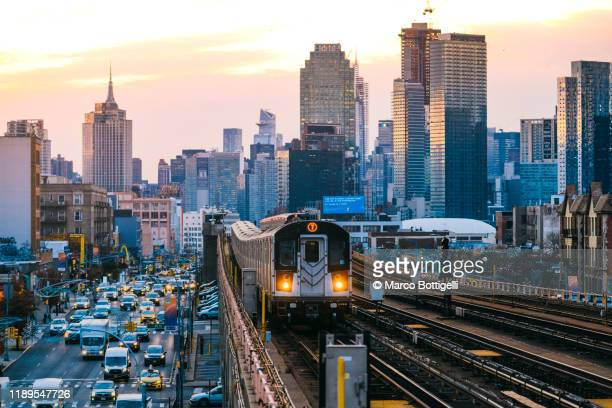 7 line subway train in queens with manhattan skyline, new york city - queens new york city stock pictures, royalty-free photos & images
