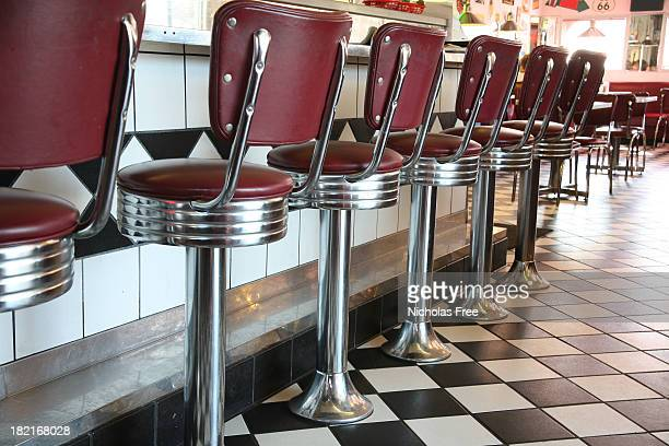 a line up of red diner style chairs  - diner stock pictures, royalty-free photos & images