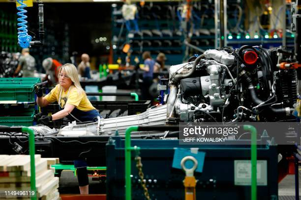 Line workers work on the chassis of full-size General Motors pickup trucks at the Flint Assembly plant on June 12, 2019 in Flint, Michigan. - GM...