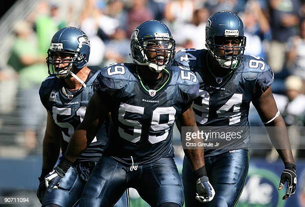 Linebacker Aaron Curry of the Seattle Seahawks celebrates with teammates Lofa Tatupu and Cory Redding after sacking quarterback Marc Bulger of the St...