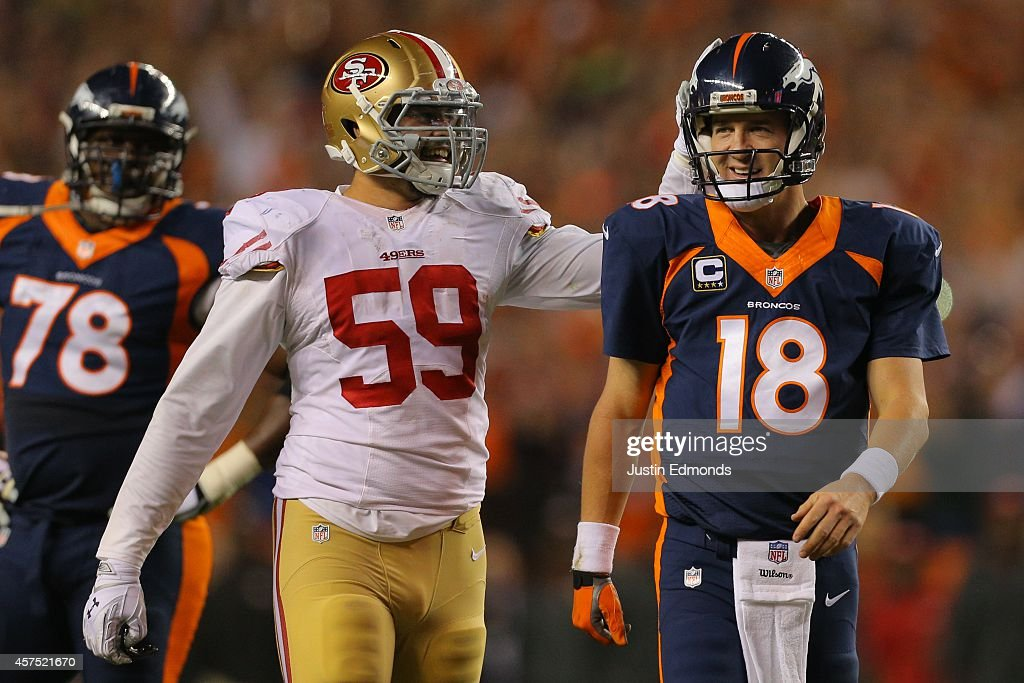 Linebacker Aaron Lynch #59 of the San Francisco 49ers congratulates quarterback Peyton Manning #18 of the Denver Broncos on his NFL-record 509th career touchdown pass in the second quarter of a game at Sports Authority Field at Mile High on October 19, 2014 in Denver, Colorado.
