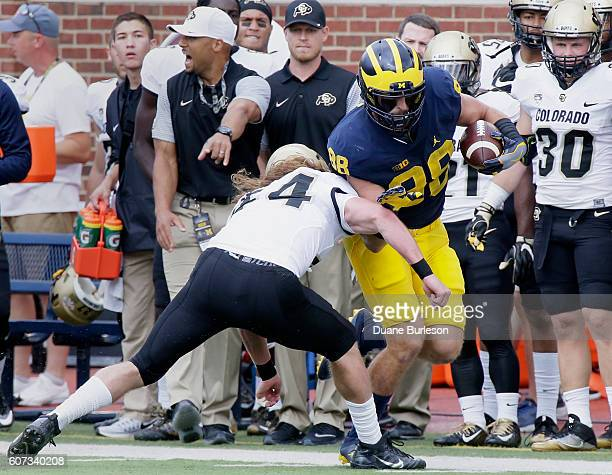 Linebacker Addison Gillam of the Colorado Buffaloes knocks tight end Jake Butt of the Michigan Wolverines out of bounds during the first half at...