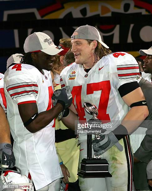 Linebacker AJ Hawks of the Ohio State Buckeyes holds his defensive player of the game award while shaking hands with teammate Santonio Holmes after...