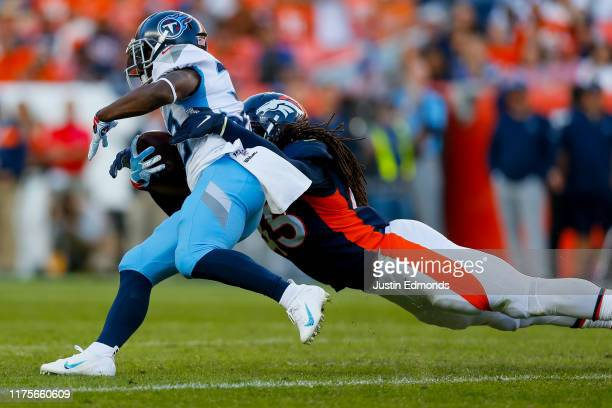 Linebacker AJ Johnson of the Denver Broncos tackles running back Dion Lewis of the Tennessee Titans during the fourth quarter at Empower Field at...
