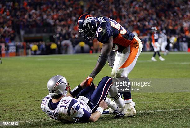 Linebacker Al Wilson of the Denver Broncos helps quarterback Tom Brady of the New England Patriots up as Brady lays on his back during the fourth...