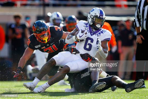 Linebacker Amen Ogbongbemiga of the Oklahoma State Cowboys brings down running back Darius Anderson of the TCU Horned Frogs in the second quarter on...