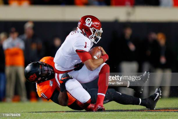 Linebacker Amen Ogbongbemiga of the Oklahoma State Cowboys brings down quarterback Jalen Hurts of the Oklahoma Sooners with a oneyard gain on...