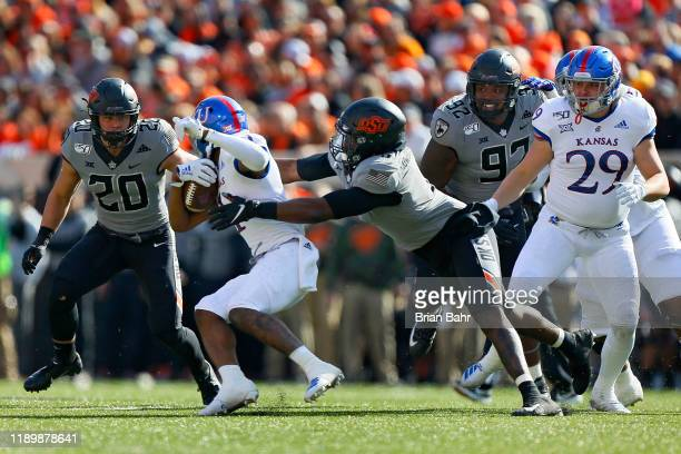 Linebacker Amen Ogbongbemiga of the Oklahoma State Cowboys catches running back Pooka Williams Jr #1 of the Kansas Jayhawks in the backfield for a...