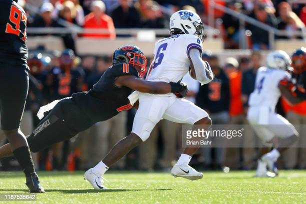 Linebacker Amen Ogbongbemiga of the Oklahoma State Cowboys dives to tackle running back Darius Anderson of the TCU Horned Frogs in the second quarter...