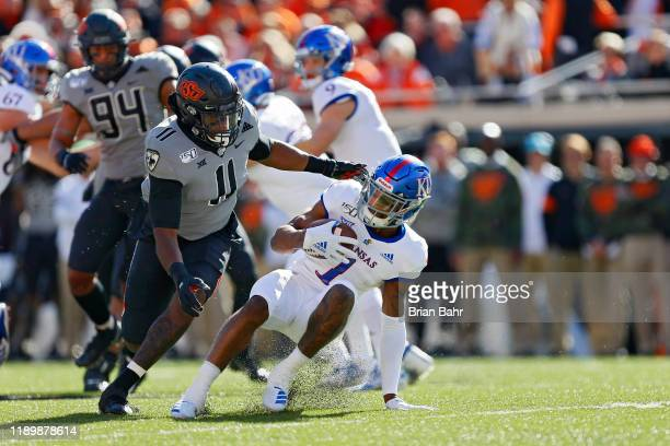 Linebacker Amen Ogbongbemiga of the Oklahoma State Cowboys forces running back Pooka Williams Jr #1 of the Kansas Jayhawks to put on the brakes in...