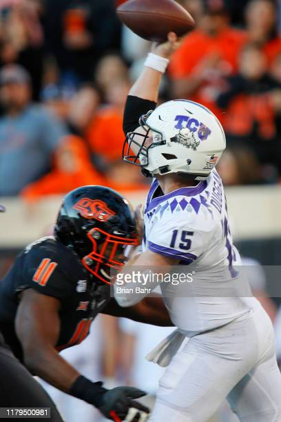 Linebacker Amen Ogbongbemiga of the Oklahoma State Cowboys hits quarterback Max Duggan of the TCU Horned Frogs in the fourth quarter on November 2...