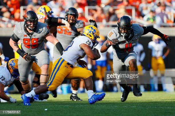 Linebacker Amen Ogbongbemiga of the Oklahoma State Cowboys keys in on running back Justin Pratt of the McNeese State Cowboys in the first quarter on...
