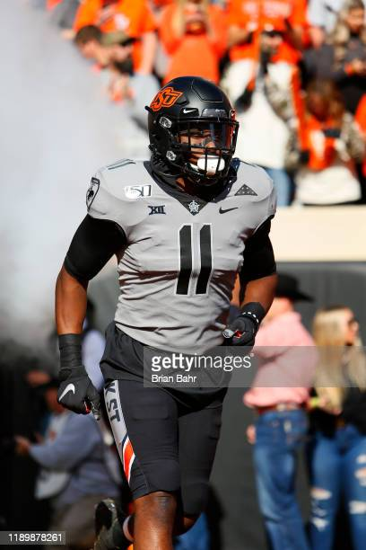 Linebacker Amen Ogbongbemiga of the Oklahoma State Cowboys runs onto the field for a game against the Kansas Jayhawks on November 16 2019 at Boone...