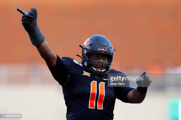 Linebacker Amen Ogbongbemiga of the Oklahoma State Cowboys signals an OSU recovery of a fumble by the Kansas State Wildcats in the first quarter on...