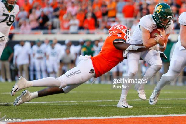 Linebacker Amen Ogbongbemiga of the Oklahoma State Cowboys tries to bring down quarterback Charlie Brewer of the Baylor University Bears on his...