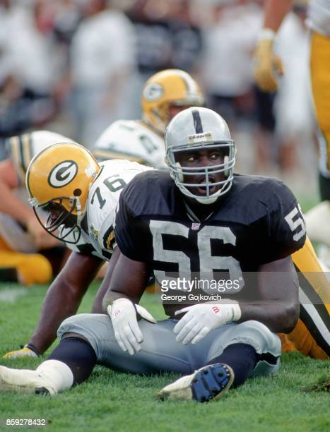 Linebacker Aundray Bruce of the Los Angeles Raiders looks on from the field after a play against offensive lineman Harry Galbreath of the Green Bay...