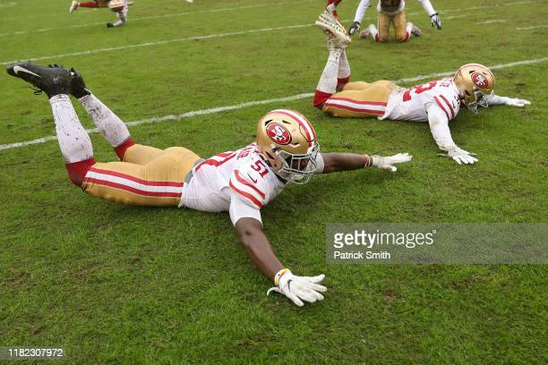 Linebacker Azeez AlShaair of the San Francisco 49ers and teammates slide on the rain soaked field after defeating the Washington Redskins 90 at...
