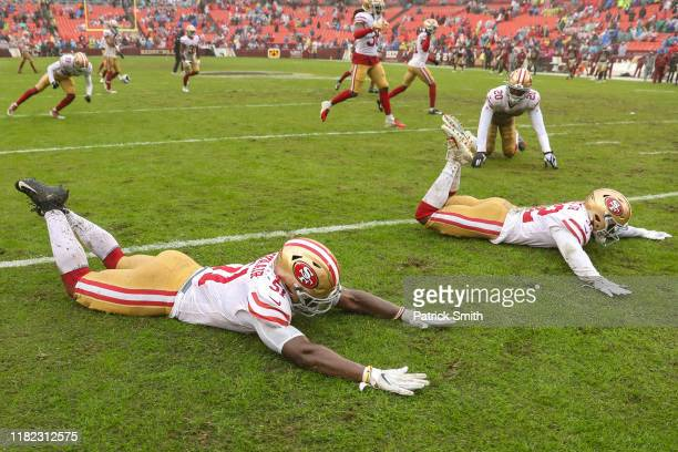Linebacker Azeez AlShaair of the San Francisco 49ers free safety DJ Reed and teammates slide on the rain soaked field after defeating the Washington...