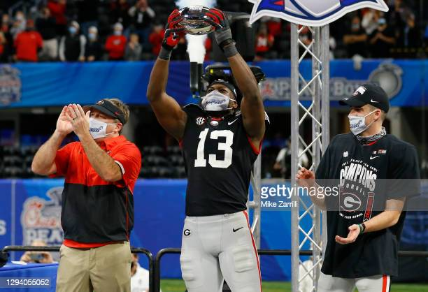 Linebacker Azeez Olujari of the Georgia Bulldogs holds the championship trophy while head coach Kirby Smart and kicker Jack Podlesny look on after...