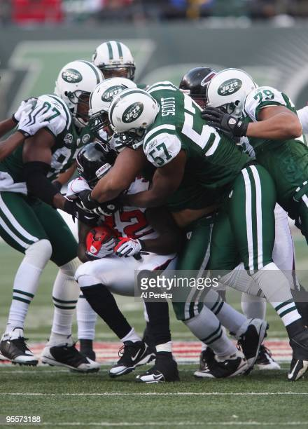 Linebacker Bart Scott Defensive Tackle Sione Pouha Linebacker Calvin Pace and Defensive End Ropati Pitoitua of the New York Jets make a gangtackle...
