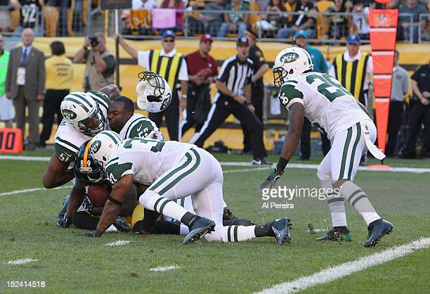 Linebacker Bart Scott loses his helmet as he and Linebacker Aaron Maybin and Safety Yeramiah Bell of the New York Jets stop Wide Receiver Jerricho...