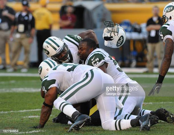 Linebacker Bart Scott of the New York Jets has his helmet knocked off as he and linebacker Aaron Maybin and safety Yeremiah Bell tackle wide receiver...