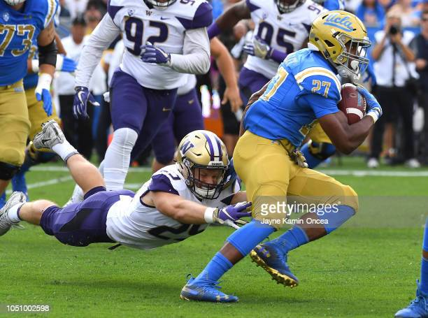 Linebacker Ben BurrKirven of the Washington Huskies chases down running back Joshua Kelley of the UCLA Bruins as he runs for a first down in the...