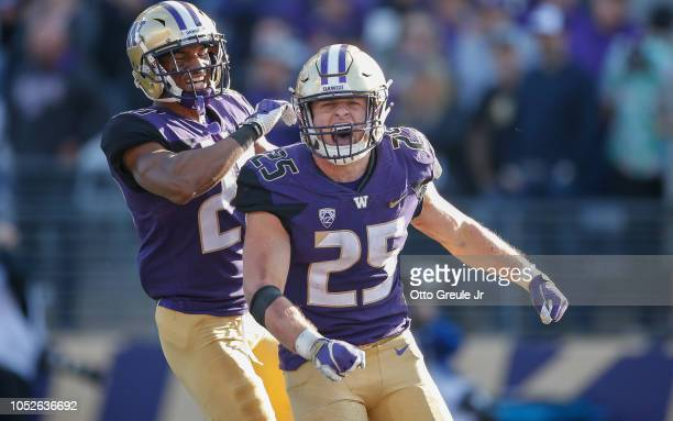 Linebacker Ben BurrKirven of the Washington Huskies is congratulated by defensive back Keith Taylor after making an interception in the fourth...