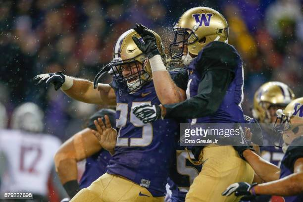 Linebacker Ben Burr-Kirven of the Washington Huskies is congratulated by defensive back Jojo McIntosh after making an interception against the...